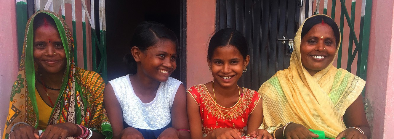 A group of women and young girls smiling