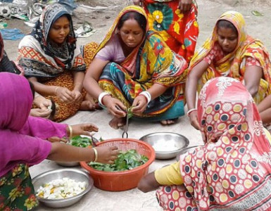 A group of women around bowls of food