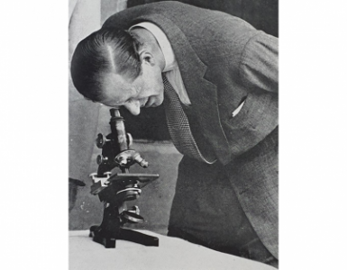 Prince Philip looking through a microscope in Nigeria